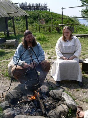 """Two Viking re-enactors in traditional summer day-wear garb tend a cook fire; Foteviken, Sweden."""