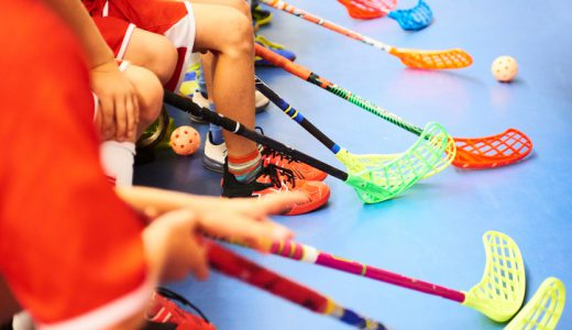 Children playing floorball. Boys holding floor ball sticks resting on the bench during a match